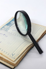 Magnifying glass and notebook