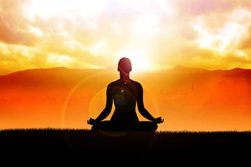 Silhouette of a woman figure meditating in the outdoors