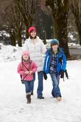 Mother Walking Two Children To School Along Snowy Street In Ski
