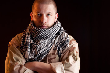 Portrait of tired soldier in camouflage, black background