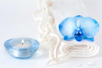 Candela con asciugamano bianco con orchidea blu