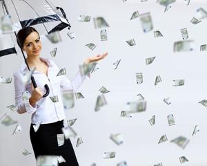 Business woman under money rain with umbrella