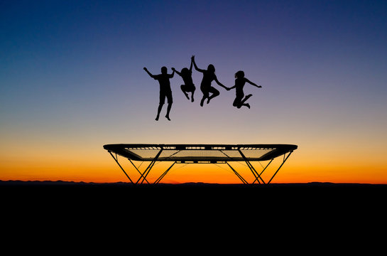 silhouette of kids on trampoline in sunset