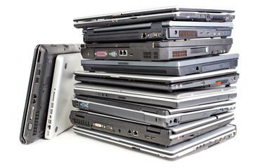 Pile of used laptops, white background