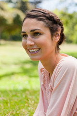 Woman looking into the distance while sitting on the grass