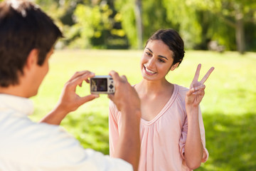 Man takes a photo of his friend giving the peace sign