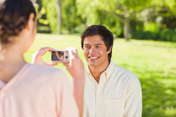 Woman takes a photo of her friend smiling