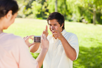 Woman takes a photo of his friend while he poses