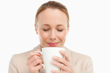 Woman in a suit smelling her tea