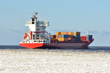 cargo container ship sailing in sea full of ice in winter