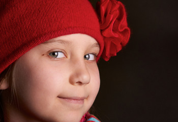 Portrait of a smiling girl, blonde in a red hat