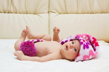 Новорождённый ребёнок лежит в шапочке и смотрит