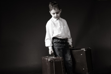 Stylized old black and white photo of a boy with big suitcases
