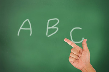 Hand hold letter on blackboard