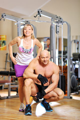 Woman in gym with personal fitness trainer