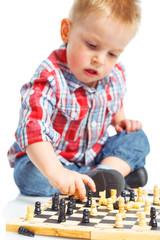 Little boy plays chess.