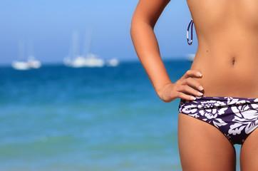 Sexy tan woman in bikini on a beach closeup