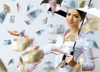 Business woman under money rain with umbrella