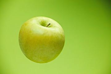 Fresh green apple on green background background