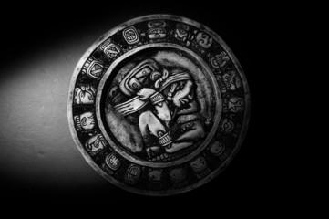 Carved Mayan calendar in dramatic light