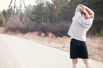 Man stretches outdoors while getting ready to run