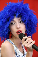 girl in  bright, blue wig, sings.