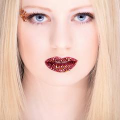Hübsche blonde Frau mit Strass Steine auf Lippen