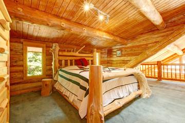 Log cabin bedroom under wood large ceiling.