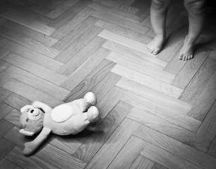 childs legs and teddy bear on the floor