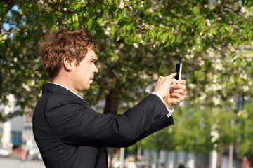 Junger Mann fotografiert mit Smartphone