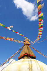 stupa with buddha eyes and prayer flags on blue sky background