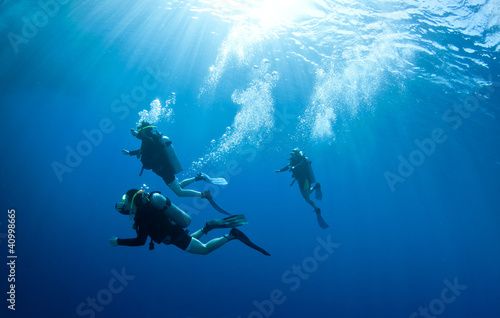Wall mural scuba divers accend from a dive