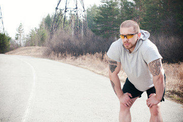 A male runner pauses during his run