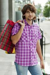 Beautiful young man after shopping. Outdoor shot