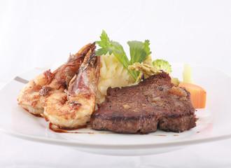 A steak and shrimp dinner over a plaid tablecloth