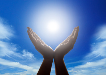 Hands holding the sun with cloudy blue sky in background
