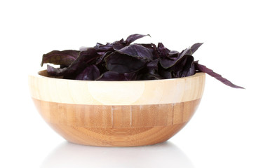 Basil in a wooden bowl isolated on white