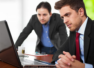 Young businessmen at a desk looking at a laptop