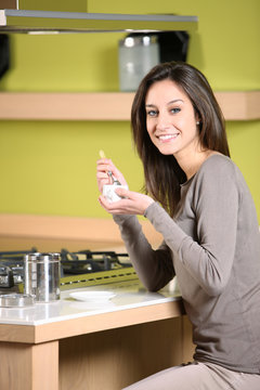 smiling woman having breakfast at home