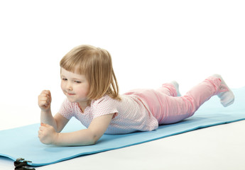 Active baby girl exercising lying on a training mat