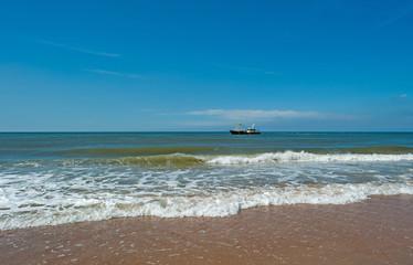 Trawler fishing at sea under a blue sky