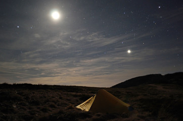yellow tent under starry sky and moonlight