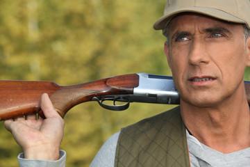 Hunter holding his shotgun over his shoulders
