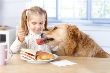 Little girl and dog having lunch together