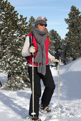 Woman walking through the snow with snow shoes