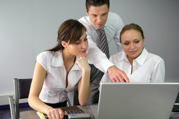 Office workers looking at a laptop