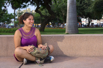 Beautiful smiling young Peruvian woman sitting in park