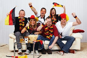 Fotobehang Amusementspark german soccer fans on the sofa