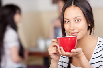 schöne junge frau mit roter kaffeetasse