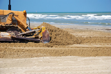 bulldozer in the sand near the sea